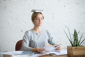 Portrait of a young woman at the desk with books on her head, sitting straight, reading a book. Education concept photo, lifestyle